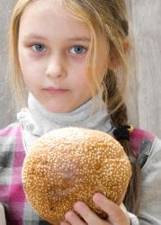 Girls saves her bread for her brothers lunch