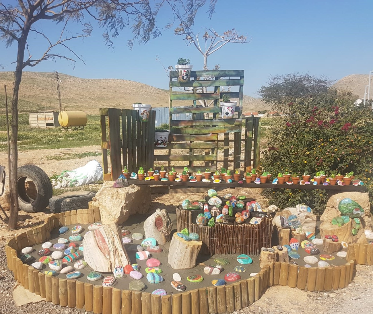Children painted flowerpots and small stones to decorate Argaman's entrance.